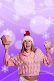 Dame blonde joyeuse dans le chapeau de Santa tenant deux Photographie stock