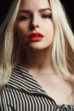 Dame blonde merveilleuse avec le maquillage lumineux et longs les cheveux posant l'OV photo stock