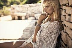 Dame blonde réfléchie leaing sur le mur en pierre Photographie stock