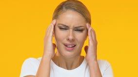 Dame bouleversée massant des temples, souffrant du désordre de migraine, mal principal banque de vidéos