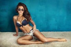 Dame bronzée de brune posant dans des lunettes de soleil. Photographie stock