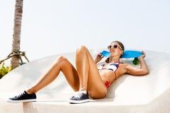 Dame bronzée sexy s'asseyant avec le panneau bleu de penny sur la plage Images stock