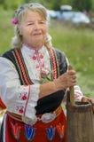 Dame bulgare faisant le fromage dans le costume traditionnel photos stock