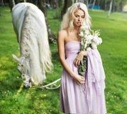 Dame calme avec le cheval et le bouquet des fleurs Photographie stock libre de droits