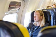 Dame caucasienne occasionnelle blonde fatiguée faisant une sieste sur le siège tout en voyageant en avion Photo libre de droits