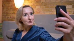 Dame caucasienne supérieure faisant des selfie-photos montrant l'embarras utilisant le smartphone en atmosphère à la maison confo image stock