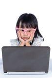 Dame chinoise asiatique ennuyeuse de petit bureau à l'aide de l'ordinateur portable Photo stock
