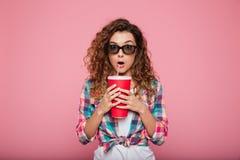 Dame choquée avec le kola et le maïs éclaté portant les lunettes 3d Photos stock