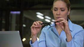 Dame concentrée d'affaires prenant des lunettes fonctionnant l'ordinateur portable, problème de vue banque de vidéos