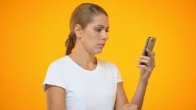 Dame contrariée mettant en rouleau la photo de smartphone, mauvaise connexion en ligne, tarif mobile clips vidéos