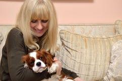 Dame Cuddling Dog Stockbilder