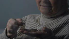 Dame déprimée pleurant comptant des pièces de monnaie près de la fenêtre grise pluvieuse, manque d'argent banque de vidéos