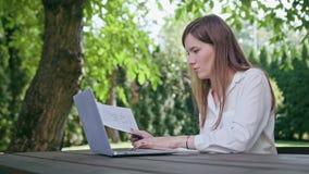 Dame d'affaires à l'aide d'un ordinateur portable dans le parc images stock