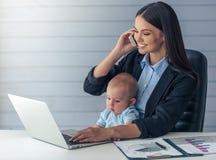 Dame d'affaires avec son bébé Photographie stock libre de droits