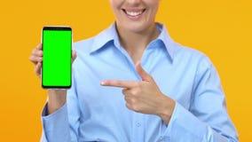 Dame d'affaires dirigeant le doigt dans le smartphone avec l'écran vert, le travail recherchant l'appli banque de vidéos