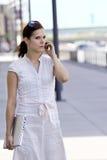 Dame d'affaires marchant avec les genoux de téléphone portable Images stock
