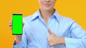 Dame d'affaires montrant le smartphone avec l'écran et les pouces verts, service en ligne banque de vidéos