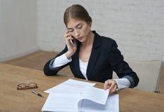 Dame d'affaires parlant du téléphone et des contrôles le sittin de rapport Photographie stock