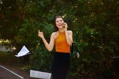 Dame d'affaires parlant sur le téléphone et le papier de lancement hors de ses mains La route à travailler, promenade par le parc images libres de droits