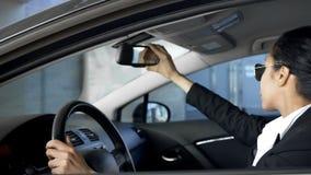 Dame d'affaires regardant dans le rétroviseur, conduisant l'automobile, règles de la circulation photographie stock
