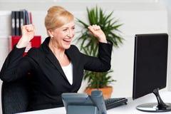 Dame de corporation Excited regardant l'écran d'ordinateur photographie stock libre de droits