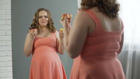 Dame de poids excessif déprimée mâchant des butées toriques devant le miroir, trouble de la nutrition banque de vidéos