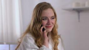Dame de sourire dans le téléphone parlant de chambre d'hôtel avec l'ami, relations de distance clips vidéos