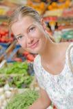 Dame de sourire dans les marchands de légumes image stock