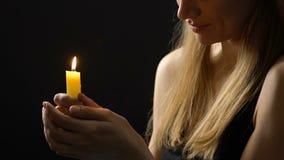 Dame de sourire paisible tenant la bougie brûlante espérant meilleur, la foi et la croyance banque de vidéos