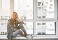 Dame de sourire prenant le repos par la fenêtre Photos libres de droits