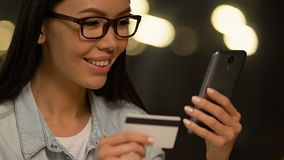 Dame de sourire utilisant la demande de réservation mobile de voyage de planification, encaissant la sécurité banque de vidéos