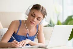 Dame in den Kopfhörern, die on-line-Vortrag notieren Lizenzfreies Stockfoto