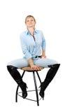 Dame in der Blue Jeans, die auf chear sitzt Stockfoto