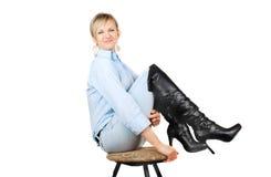 Dame in der Blue Jeans, die auf chear sitzt Stockfotografie