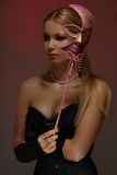 Dame an der Maskerade mit rosafarbener Schablone Stockfoto
