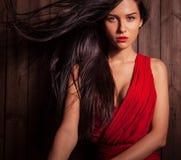 Dame in der roten Haltung auf hölzernem Hintergrund Stockbild