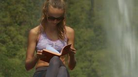 Dame in der violetten Spitze liest Tagebuchbuch auf großem Felsen stock footage