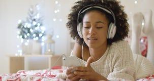 Dame in der weißen Strickjacke auf Bett hörend Musik Lizenzfreies Stockfoto