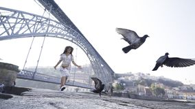 Dame die aan duiven op dijk dichtbij brug lopen stock footage