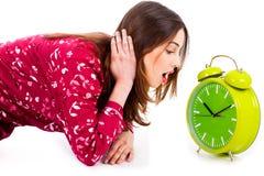 Dame, die Alarmuhr betrachtet Stockfotografie