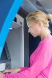 Dame die ATM in tegenovergestelde richting gebruiken royalty-vrije stock afbeeldingen