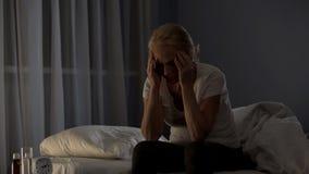 Dame, die auf dem Bett, unfähig, wegen der schweren Migräne und der Schlechtschmerz einzuschlafen sitzt stockfotografie