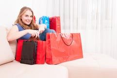 Dame, die auf der Couch findet Sachen in den Einkaufstaschen sitzt Lizenzfreie Stockfotografie