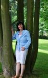 Dame, die auf einem Baum sich lehnt Stockfotos