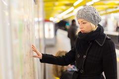 Dame, die auf Kartenplatte der öffentlichen Transportmittel schaut lizenzfreies stockbild