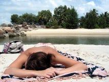Dame, die auf Strand suntanning ist Stockfotos
