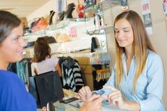 Dame die bij controle door creditcard betalen stock afbeeldingen