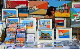 Dame, die bunte Drucke auf einem Marktstall verkauft Stockfotografie