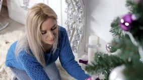 Dame die de Kerstmisboom met kaarsen verfraaien stock video