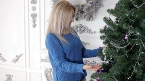 Dame die de Kerstmisboom met snuisterijen en gebieden verfraaien stock footage